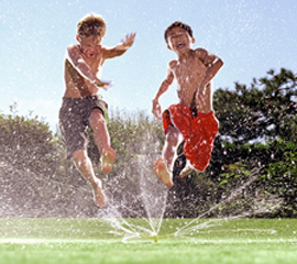 Kids Jumping Through Sprinkler